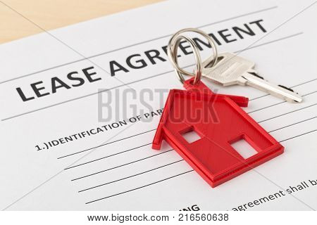 House door key with red house key chain pendant and lease agreement form on wooden desk - house or apartment rental concept