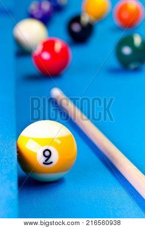 Billiard pool game nine ball with nineball balls and cue on billiard table with blue cloth selective focus on nine ball