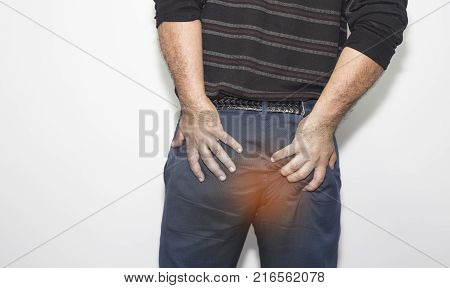 Man with hemorrhoids holding his ass in pain, in a white background