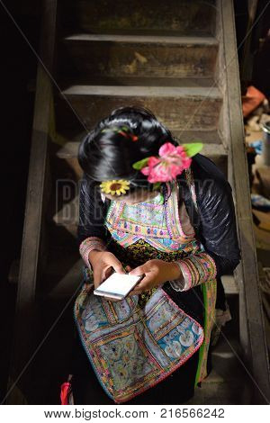 Mia tribe girl dressed in traditional costumes chats on the cellular phone