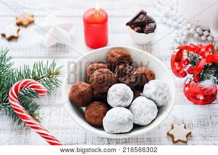 Chocolate truffles in white bowl. Christmas sweets, Christmas chocolate candies on white table. Closeup view