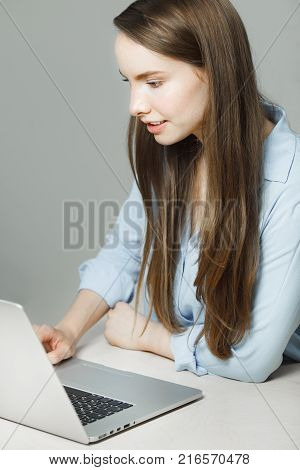 Young woman with long hair dressed in classic shirt sits at modern laptop involved in work portrait photo. Businesswoman does her job at computer.