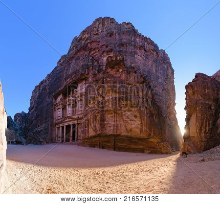 Panorama of the Siq (corridor) and Al-Khazneh (Treasury) carved in rock in Petra Jordan at sunset.
