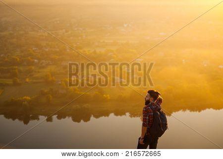 Bearded man in checkered shirt enjoying breathtaking view.