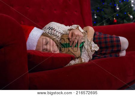 Smiling teen girl is sleeping sweetly on the couch near a Christmas tree with gifts in her hands - in anticipation of a miracle on a merry Christmas.