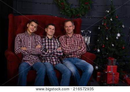 Cheerful friends in a plaid shirts are sitting on a couch in front of a Christmas tree in anticipation a merry Christmas.