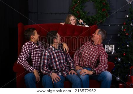 Joyful friends in a plaid shirts are sitting on a couch in front of a Christmas tree and look back at the teenage girl with the phone - in anticipation a magic on a merry Christmas.
