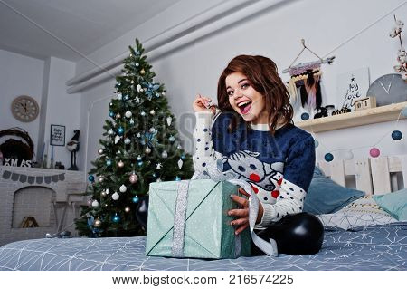 Girl Wear Warm Sweater Sitting On The Bed Against New Year Tree With Presents Box At Hands On Studio
