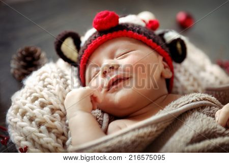 Sweet baby boy sleeping at home in Christmas eve, wearing funny reindeer hat, Rudolph costume, happy Christmas time