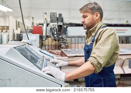 Side view portrait of mature workman  operating machines in industrial shop standing by mechanical control panel and pushing buttons, copy space