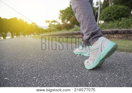 Road to successrunning on road with sports shoeshealthy lifestyle sports woman running female legs with sneakers jogging in evening prepare for marathon