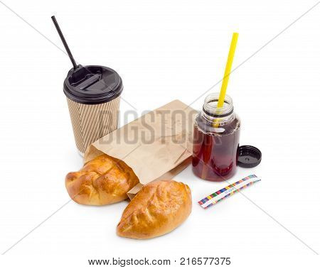 Two small pies with sweet toppings in fast food brown paper bag tea in the plastic container and disposable paper cup with plastic lid and drinking straws on a white background