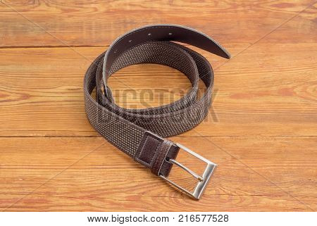 Casual brown elastic stretch belt for men with leather ends and classical buckle on an old wooden surface