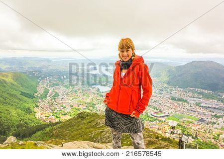 Happy young caucasian tourist in scenic norwegian landscape and popular landmark. Hiking on Mount Ulriken. Norwegian tourism highlight. Bergen urban cityscape. Traveler woman in North Europe.