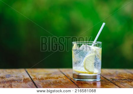 Glass glass. Lemon. Mineral water with ice. Cocktail straw. A green backgroundA green background