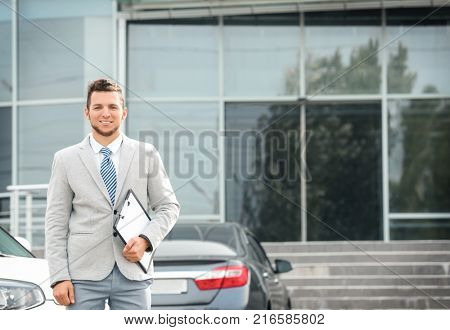 Salesman standing near new car outdoors