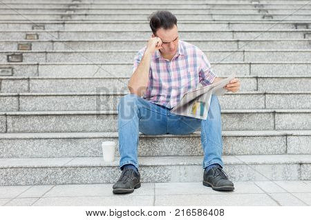 Closeup portrait of tensed young man reading newspaper and sitting on stairway outdoors. Front view.