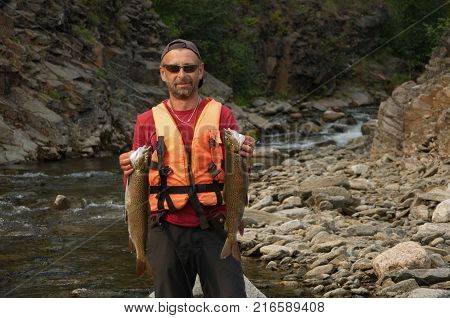 Fisherman holding two large asiatic trouts on the shore of the wild Siberian river.
