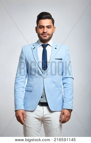 Vertical portrait of a handsome young stylish man wearing white trousers and blue jacket on grey background style fashion confidence masculinity youth concept.