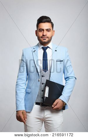 Attractive young stylish man posing confidently on grey background wearing blue jacket white trousers and vintage vest holding a clipboard professional leadership youth confidence success style.