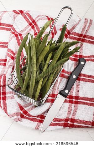 green organic beans in a metal basket and a knife to cut