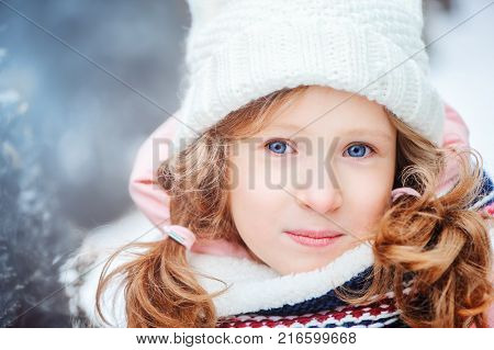 winter portrait of 8 years old kid girl walking outdoor in snowy day wearing white knitted hat and pink coat