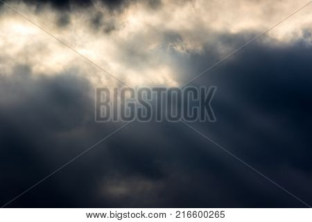 Moody dark sky. Soft background image with crepuscular rays of sunlight through cloud. Natural light and dark variegated texture backdrop.