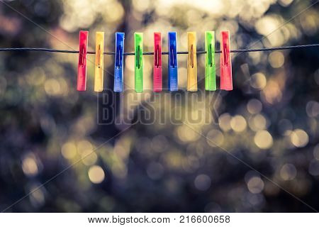Colorful pegs hanging on clothesline. Cross processing effect applied