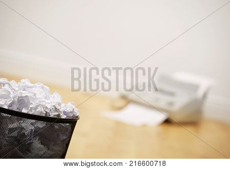 Waste Paper Bin Full Of Crumpled Paper And Fax Machine On Wood O