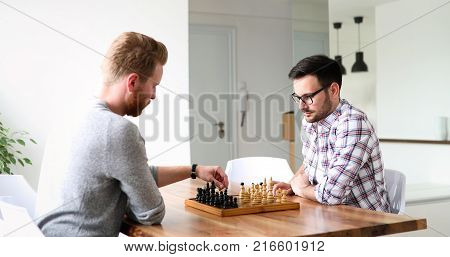 Portrait of two young man playing intelligent game of chess