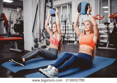 Dumbbells. Girls are engaged in a group a body of bodybuilding with dumbbells. Elbow bending at the elbow