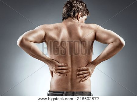 Kidneys pain or lower back pain. Man holding his back. Medical concept.