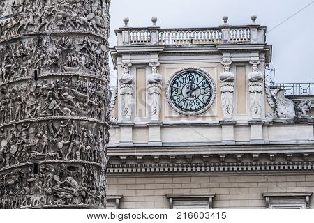 detail of the Chigi palace clock with Colonna of Marcus Aurelius, Column of Marcus Aurelius, on Square Column. Rome. Italy.