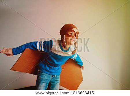 little boy with pilot glasses and wings play fly at home, child dreams concept