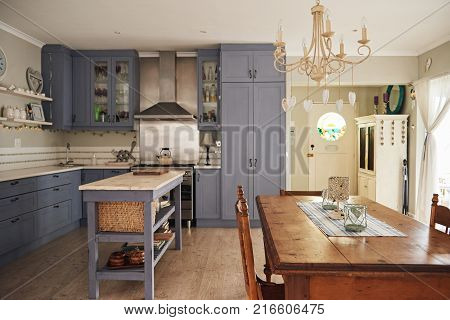 Interior of a country style kitchen with an island, dining table and modern appliances in a residental home