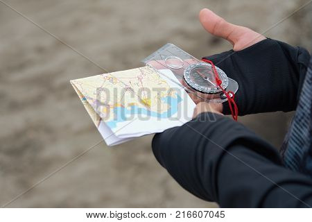 Man holding map.Athlete uses navigation equipment for orienteering,compass and topographic map