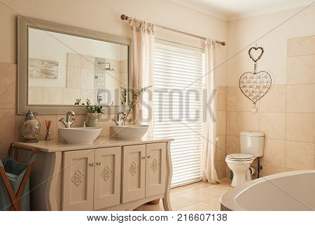 Interior of an empty country style bathroom with basins, a toilet and bath in a contemporary residential home