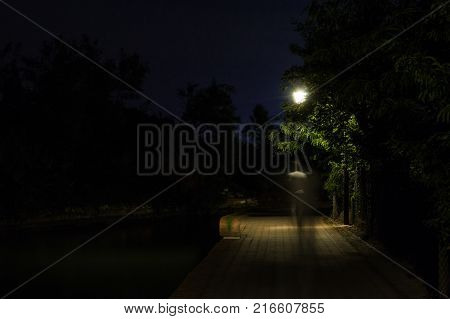 Double exposure night scene of person walking dark street illuminated with streetlights. The receding male silhouettes on the road in the park. Human figure in motion blur going along the city river. Long shutter.