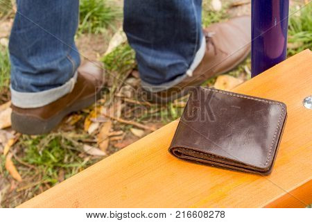 The man lost his wallet with money. Men leave and only the legs and shoes are out of focus and the leather brown purse on the scroll