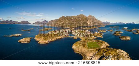 Aerial view of Henningsvaer, its scenic football field and mountains in the background. Henningsvaer is a fishing village located on several small islands in the Lofoten archipelago in Norway.