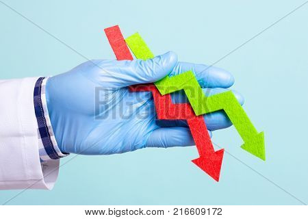 The doctor holds green and red arrow in his hand falls down. Indicators deteriorate the fall is expected