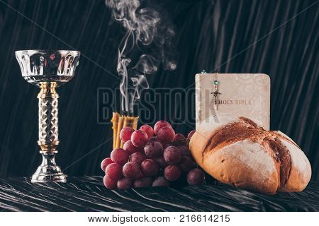 open holy bible christian cross and chalice on table Holy Communion