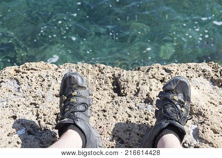 A stone slab near the sea. The texture of the water and stone. The weather is nice. Feet in sneakers.