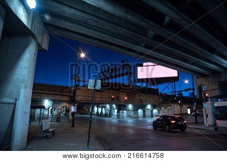 Gritty dark Chicago city street intersection under industrial train bridge viaduct tunnel and highway with CTA bus stops at night.