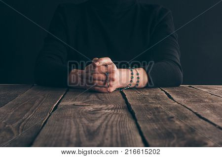 cropped image of nun sitting at table with rosary and praying