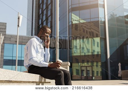 Happy black businessman talking on smartphone and drinking take away coffee outdoors. Young african-american salesman working with mobile near business centre on the bench in urban area cityscape