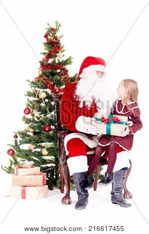 Cute little girl receiving gift from Santa Claus sitting on his lap near Christmas tree