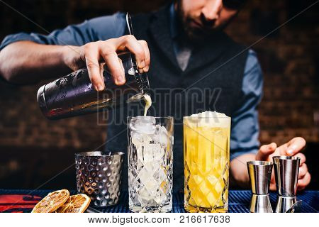 Barman Preparing And Pouring Red Cocktail In Martini Class. Cosmopolitan Cocktail With Bar Backgroun