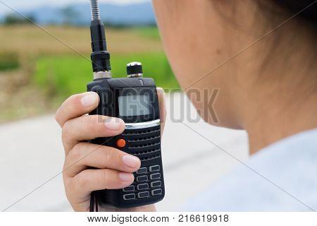 walkie-talkie radio in handLook over shoulder.Communicate with radio