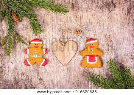 Homemade Christmas gingerbread in the shape of little men. Gingerbread men on Christmas background with fir tree.